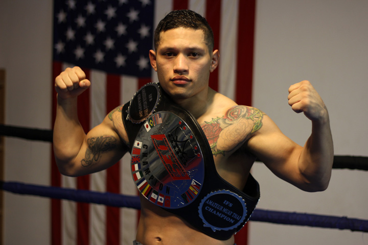 With his IFS Championship belt draped across his shoulder, Victor Saravia strikes a fight pose in the boxing ring.