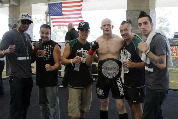 Wearing his IFS Championship belt, Jules Wallace celebrates his win with members of his team and IFS promoter Shawn Shilati in the boxing ring.