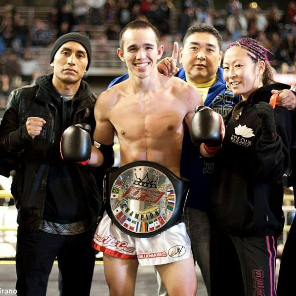 Wearing his IFS Championship belt, Daniel McDonald celebrates his win with members of his team in the boxing ring.