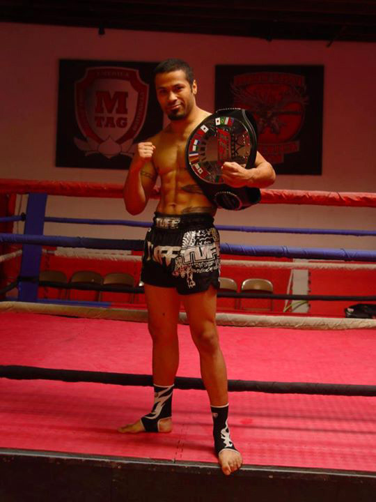 Eduardo Alvarado strikes a fight pose in the boxing ring with his IFS Championship belt draped over his shoulder.