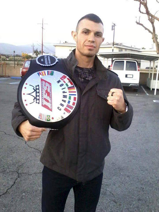 Rene Orozco strikes a fist pump with his IFS Championship belt draped over his shoulder.