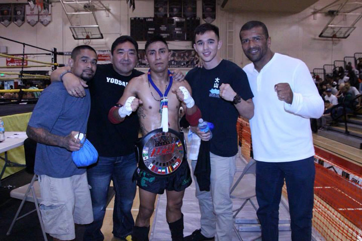 Wearing his IFS Championship belt, Oscar Sanchez celebrates his win with members of his team.