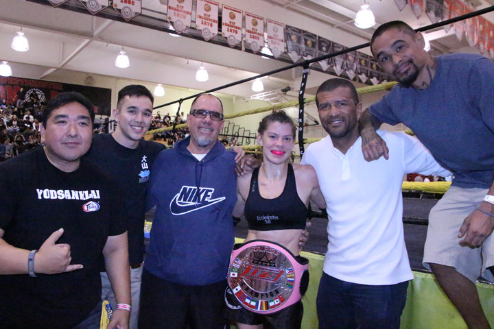 Wearing her IFS Championship belt, Lisa Mauldin celebrates her win with members of her team.
