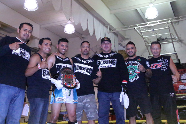Wearing his IFS Championship belt, Jay Alvarez celebrates his win with members of his team and IFS promoter Shawn Shilati.