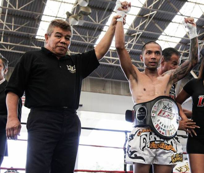 Wearing his IFS Championship belt, Luis Reyes celebrates his win as the IFS referee raises Reyes' hand as the winner.