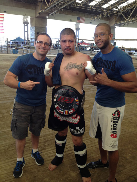 Wearing his IFS Championship belt, Arturo Avila celebrates his win with members of his team.
