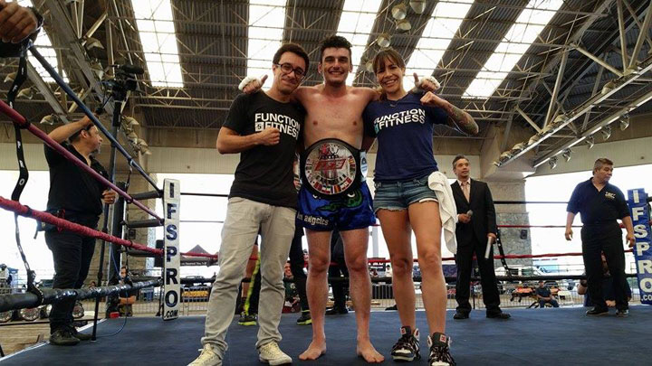 Wearing his IFS Championship belt, Andre Keshishyan celebrates his win with members of his team in the boxing ring.
