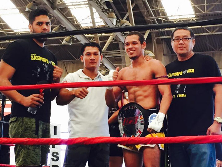 Wearing his IFS Championship belt, Marquis Ross celebrates his win with members of his team in the boxing ring.