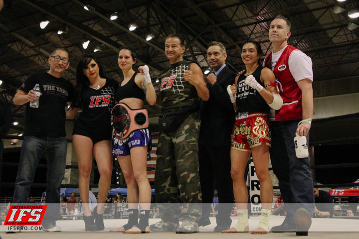 Wearing her IFS Championship belt, Natalie Morgan celebrates her win with the IFS in the boxing ring.