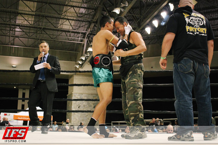 Wearing his IFS Championship belt, Chris Mendoza celebrates his win with IFS promoter Shawn Shilati in the boxing ring.