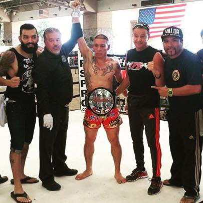 Wearing his IFS Championship belt, Said Sanchez celebrates his win with members of his team and the IFS in the boxing ring.
