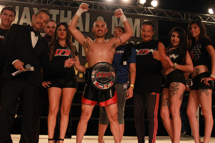 Wearing his IFS Championship belt, Gustavo Del Valle celebrates his win with his team and the IFS in the boxing ring.