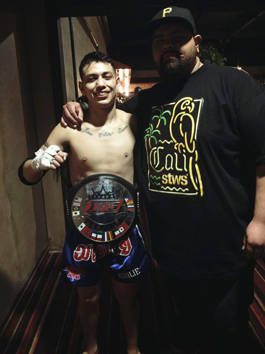 Wearing his IFS Championship belt, Robert Hernandez celebrates his win by posing with a supporter.