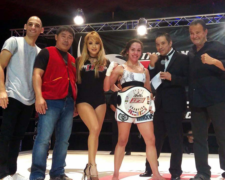 Wearing her IFS Championship belt, Magalie Alvarez celebrates her win with members of her team and the IFS in the boxing ring.