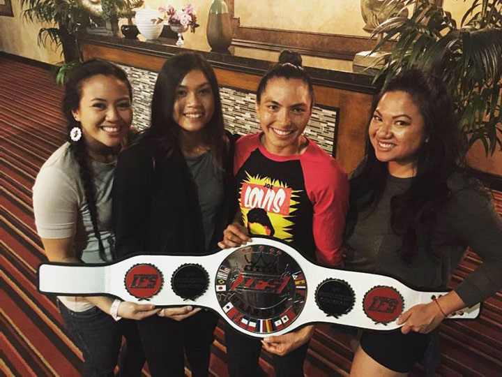 Janet Todd poses with members of her team who share in holding her IFS Championship belt in the lobby.