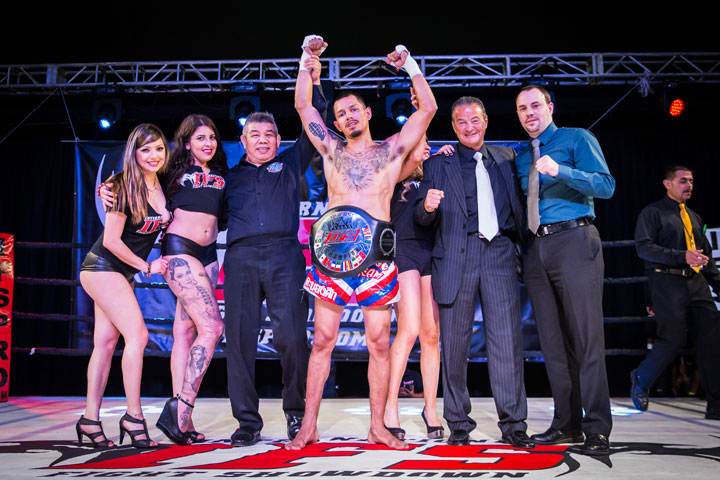 Wearing his IFS Championship belt, Michael Avilex celebrates his win with the IFS in the boxing ring.