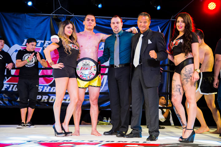 Wearing his IFS Championship belt, Robert Reiner celebrates his win with the IFS in the boxing ring.