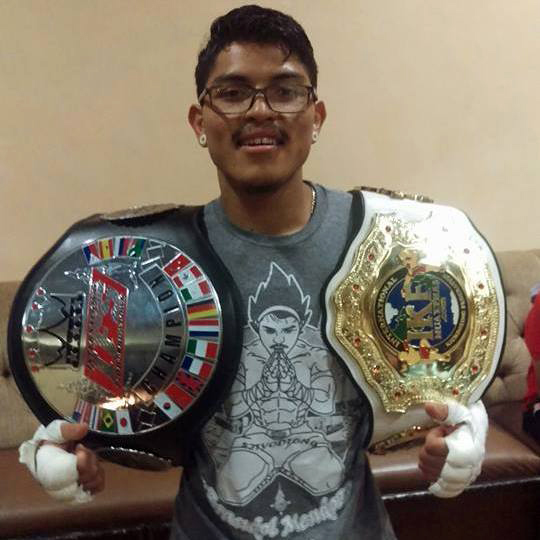 Brandol Mendoza with the IFS Championship belt draped over one shoulder and the IKF Championship belt over his other.
