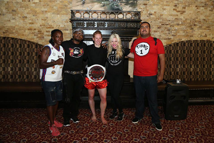 Wearing her IFS Championship belt, Alyshia Madison poses with members of her team in the lobby.