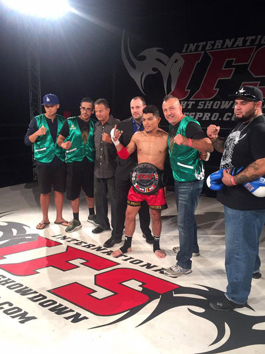 Wearing his IFS Championship belt, Brandol Mendoza celebrates his win with members of his team and the IFS in the boxing ring.