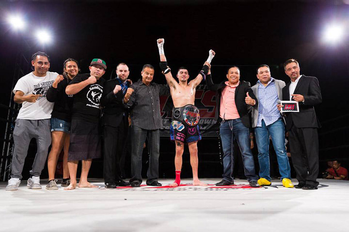 Wearing his IFS Championship belt, Andres Esparza celebrates his win with members of his team and the IFS in the boxing ring.