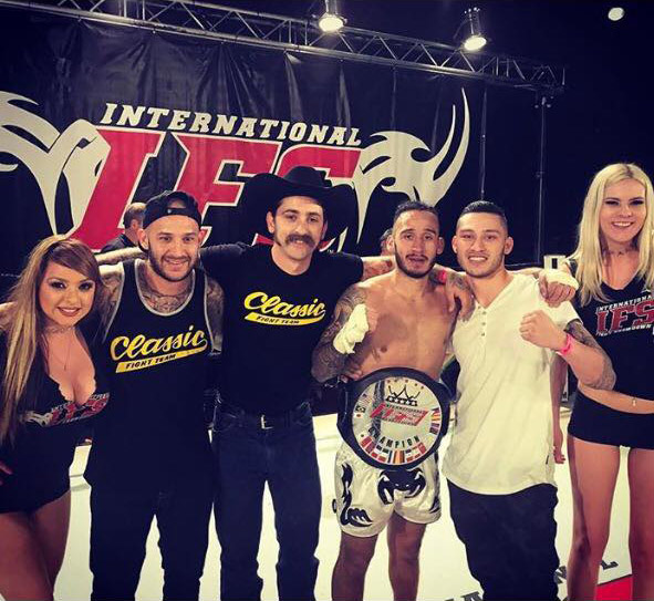 Wearing his IFS Championship belt, Chris Paez celebrates his win with members of his team and the IFS ring girls in the boxing ring.