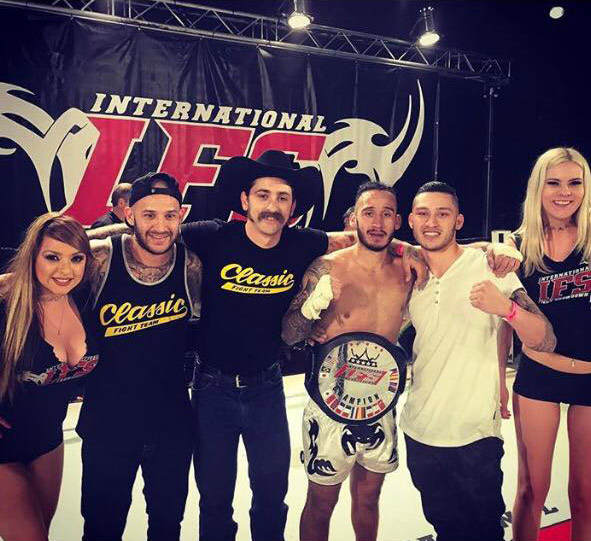 Wearing his IFS Championship belt, Chris Paez celebrates his win with members of his team and the IFS ring girls the boxing ring.