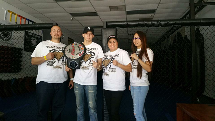Wearing his IFS Championship belt over his shoulder, Brandon Rivera poses with members of his team.