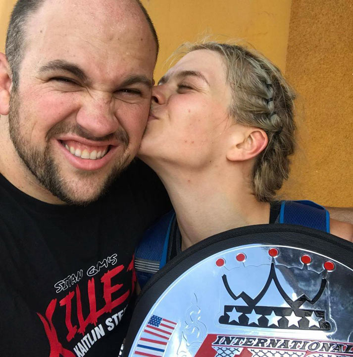 Kaitlin Stein celebrates her win with her IFS Championship belt and a kiss.
