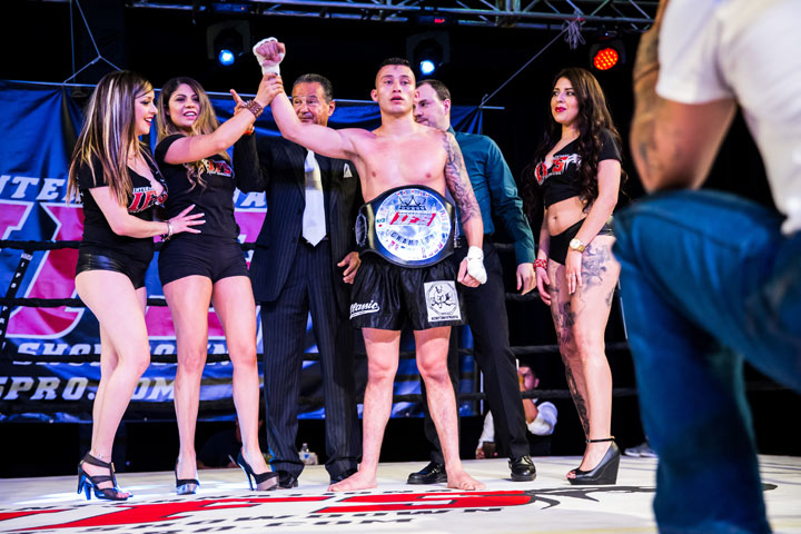 Wearing his IFS Championship belt and surrounded by IFS ring girls, Diego Paez celebrates his win with  the IFS in the boxing ring.