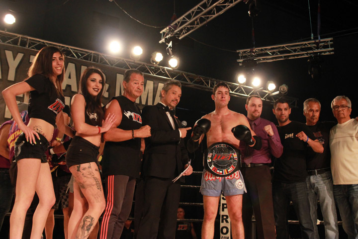 Wearing his IFS Championship belt, Lance Dixon celebrates his win with members of his team and the IFS in the boxing ring.
