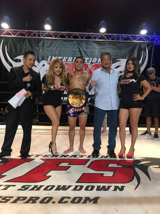 Wearing his IFS Championship belt, Gilbert Nakatani celebrates his win with members of the IFS in the boxing ring.