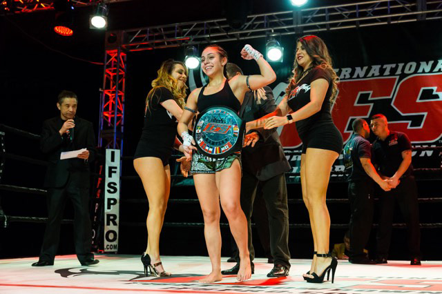 Wearing her IFS Championship belt, Kennedy Maze celebrates her win flanked by the IFS ring girls in the boxing ring.