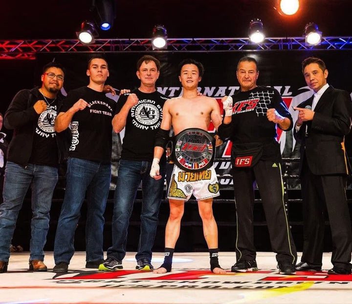 Wearing his IFS Championship belt, Jason Kang celebrates his win with members of his team and the IFS in the boxing ring.