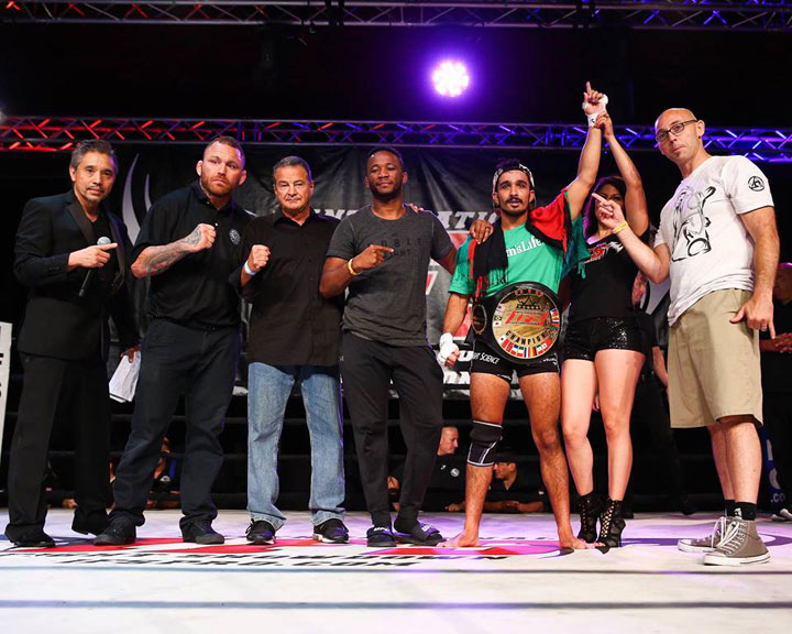 Wearing his IFS Championship belt, Ali Navaz celebrates his win with members of his team and the IFS in the boxing ring.
