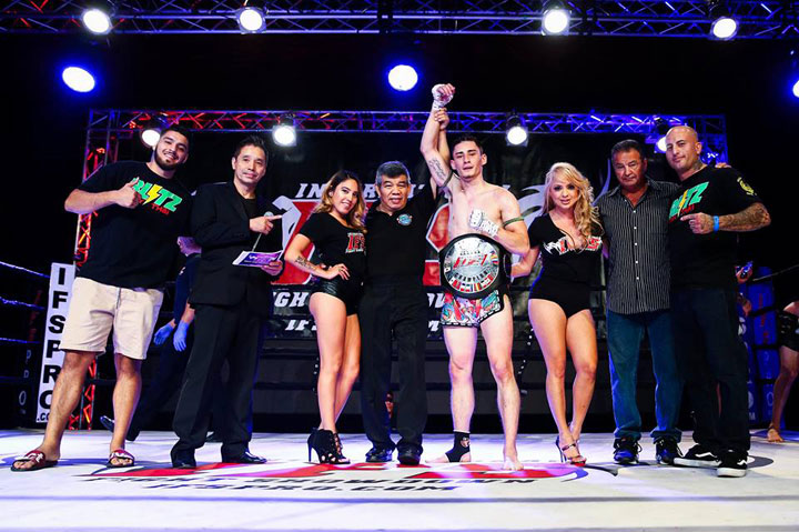 Wearing his IFS Championship belt, Dane Turney celebrates his win with members of his team and the IFS in the boxing ring.