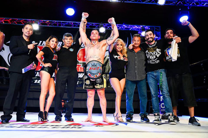 Wearing his IFS Championship belt, Vincent Familari celebrates his win with members of his team and the IFS in the boxing ring.