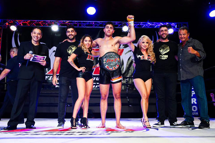 Wearing his IFS Championship belt, Ryan Fathi celebrates his win with members of his team and the IFS in the boxing ring.