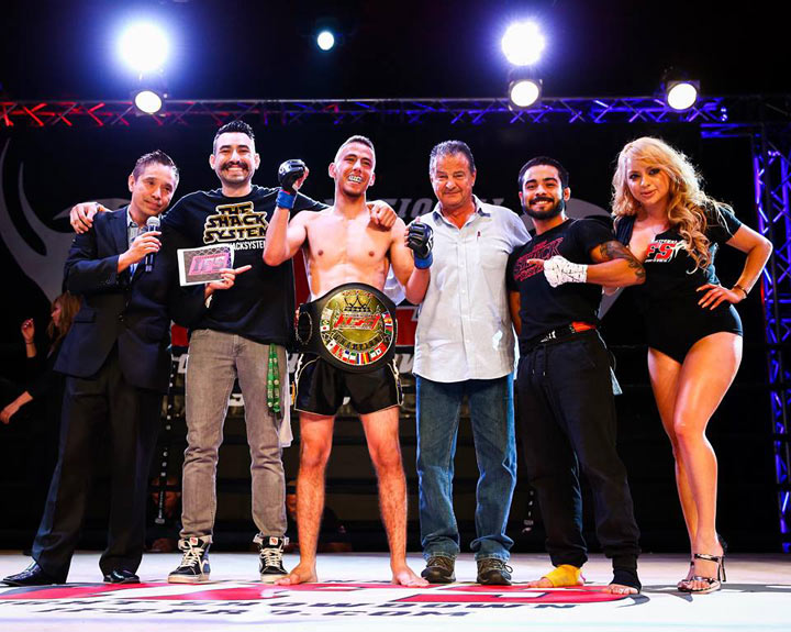 Wearing his IFS Championship belt, Jesse Velazquez celebrates his win with members of his team and the IFS in the boxing ring.