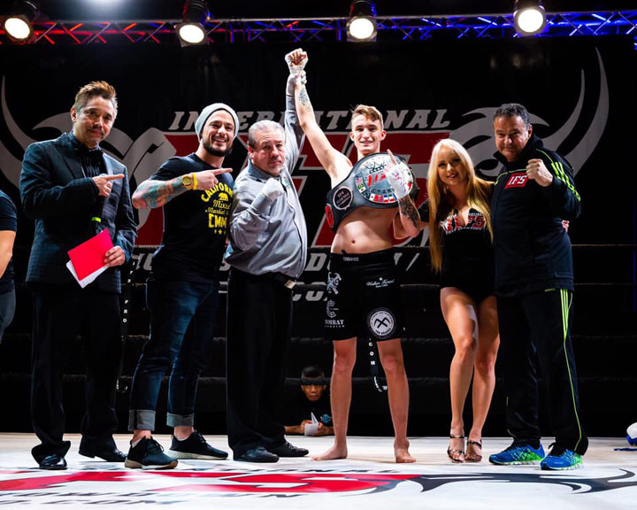Wearing his IFS Championship belt, Dalton Durden celebrates his win with members of his team and the IFS in the boxing ring.