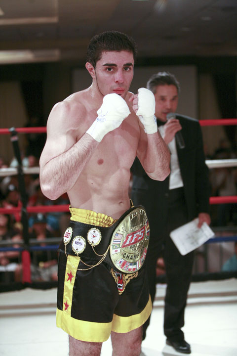 Wearing his IFS Championship belt, Sevak Ohanjanian celebrates his win by striking a fight pose in the boxing ring.