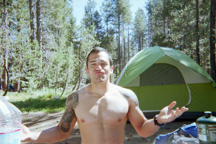 Jonathan Chester standing outdoors while camping.
