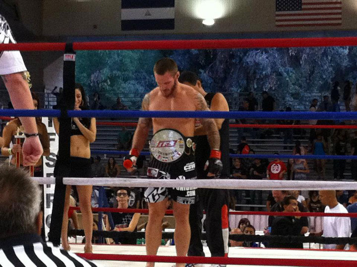 Ben Jones receives IFS Championship belt around his waist in the boxing ring.