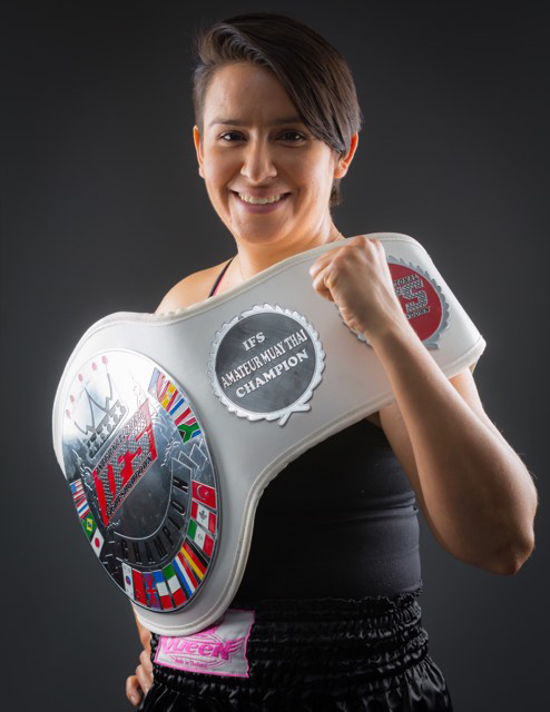Crystal Laguna poses with her IFS Championship belt draped like a sash around her shoulder and waist.