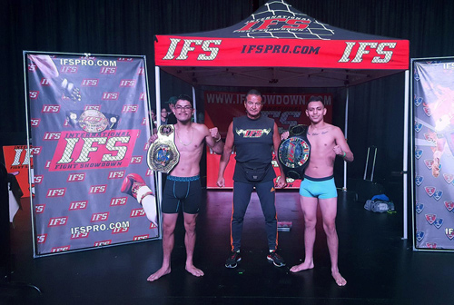 Two competitors posing with IFS fight promoter in front of backdrop banners.